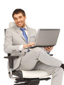 Young businessman sitting in chair with laptop — Stock Photo