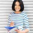 Happy and smiling teenage girl with big notepad — Stock Photo #10833267