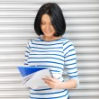 Happy and smiling teenage girl with big notepad — Stockfoto