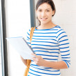 Happy and smiling teenage girl with big notepad - Stockfoto
