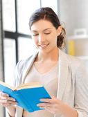 Happy and smiling woman with book — Zdjęcie stockowe
