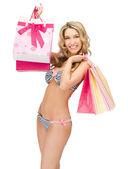 Förförisk kvinna i bikini med kassar och påsar — Stockfoto