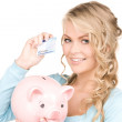 Lovely woman with piggy bank and money — Stock Photo #11757588