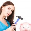 Teenage girl with piggy bank and hammer — Stock Photo