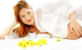 Smiling pregnant beauty with flowers — Stockfoto