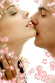 Gentle kiss with flowers — Stock Photo