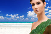 Woman with green leaf on tropical beach — Stock Photo