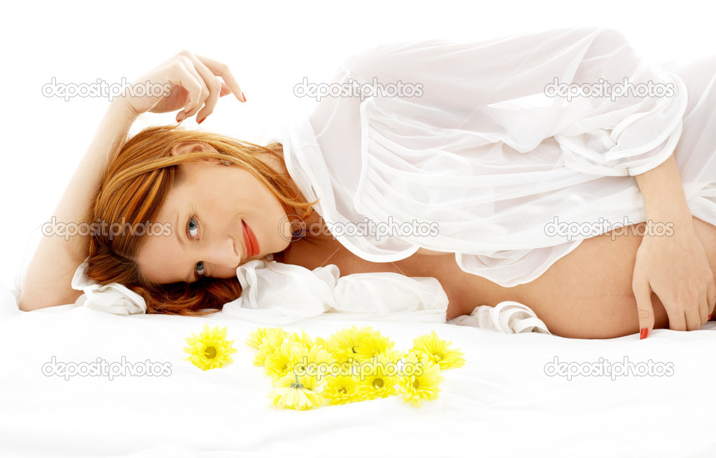 Beautiful pregnant woman with yellow flowers in bed — Stock Photo #11757152