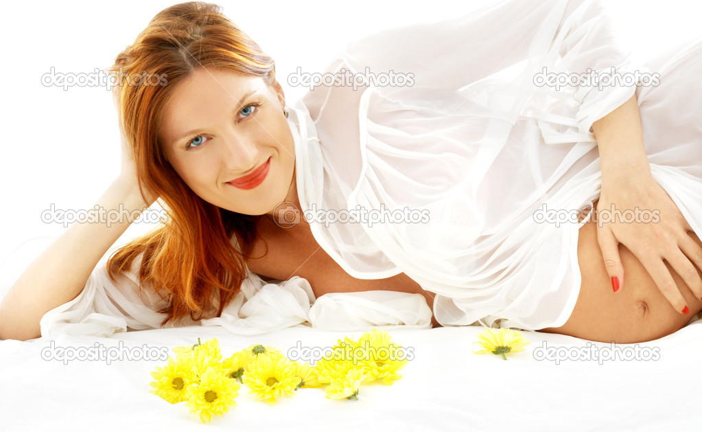 Beautiful pregnant woman with yellow flowers in bed  Stock Photo #11757155