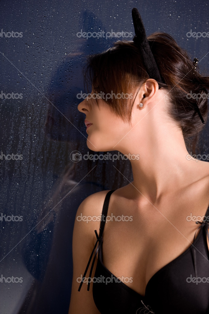 Sad woman with cat ears at the rainy window — Stock Photo #11759124
