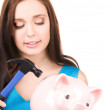 Teenage girl with piggy bank and hammer — Stock Photo #11760752