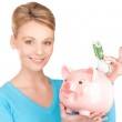 Lovely woman with piggy bank and money — Stock Photo #11760869