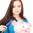 Teenage girl with piggy bank and hammer — Stock Photo #11760950