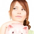 Lovely teenage girl with piggy bank — Stock Photo #11761889