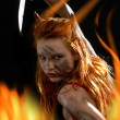 Red devil girl with a knife in fire - Stock Photo