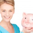 Lovely woman with piggy bank — Stock Photo #11762817