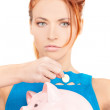 Lovely woman with piggy bank - Stok fotoğraf