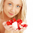 Happy blond in spa with red and white rose petals — Stock Photo