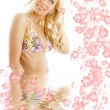 Tanned blond in colorful bikini standing in water with flowers — Stock Photo