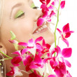 Happy blond with orchid — Stockfoto