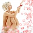 Naked blond with rose petals and flowers in water — Stock Photo