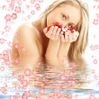 Blond with red and white rose petals in water with flowers  — Stock Photo
