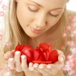Lovely blond in water with red rose petals - Stock Photo