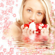 Happy blond in water with red and white flowers - Stock Photo