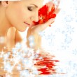 Lady with red petals and snowflakes in water — Stock Photo