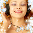 Christmas picture of smiling redhead listening music with snowflakes - Stock Photo
