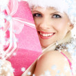 Santa helper girl with pink gift box and snowflakes - Stock Photo