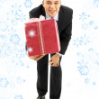 Businessman with pink gift package and snowflakes — Stock Photo