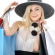 Portrait of blond in hat with shopping bags — Stock Photo