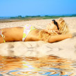 Tanning blonde in sunglasses — Stock Photo