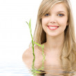 Blue-eyed blonde with bamboo in water — Stock Photo #11766655