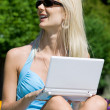 Outdoor picture of lovely blonde with laptop — Stockfoto