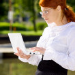 Businesswoman with laptop in the park — Stock Photo #11766997