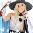 Portrait of blonde in hat with shopping bags - Stock Photo