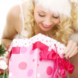 Lovely santa helper girl with christmas gifts — Stockfoto