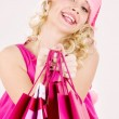 Cheerful santa helper girl with shopping bags — Stock Photo #11768010