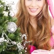 Santa helper girl with gift box and christmas tree — Stock Photo #11768073