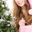 Santa helper girl with gift box and christmas tree — Stock Photo #11768077