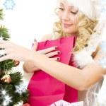 Santa helper girl decorating christmas tree — Stock Photo #11768124