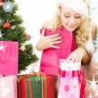 Santa helper girl with gifts and christmas tree — ストック写真