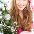 Santa helper girl with gift box and christmas tree — Stock Photo #11768216