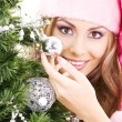Santa helper girl decorating christmas tree — Stock Photo #11768484