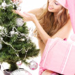Santa helper girl decorating christmas tree — Stock Photo