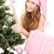 Santa helper girl decorating christmas tree — Stock Photo #11768486
