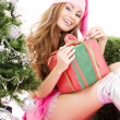 Santa helper girl with gift box and christmas tree — Stock Photo #11768831