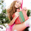 Santa helper girl with gift box and christmas tree — Stock Photo #11768906